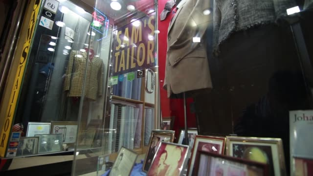 signage for sams tailor is displayed outside the companys store, manu melwani, co owner of sams tailor, right, looks out from the entrance,... - tape measure video stock e b–roll