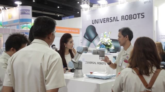 vídeos de stock, filmes e b-roll de signage for universal robots a/s is displayed at the company's booth during the manufacturing expo 2016 in the bangkok international trade exhibition... - enfoque de objeto sobre a mesa