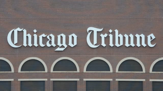 signage hangs outside the chicago tribune printing facility in chicago, illinois, us, close up shot pans across the chicago tribune signage mounted... - torre del tribune video stock e b–roll