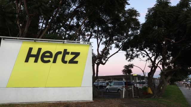 Signage is displayed at dusk outside of a Hertz Global Holdings Inc rental location at Los Angeles International Airport in Los Angeles California US...