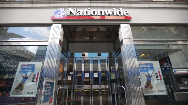 signage is seen above a nationwide building society branch in london, u.k, on monday, aug. 12 a customer uses an automated teller machine outside a... - financial accessory stock videos & royalty-free footage
