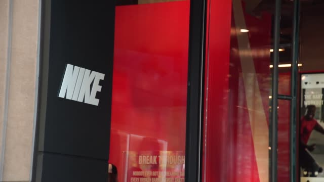 signage sits on display as customers walk in and out of revolving door at a nike store in downtown chicago il on sunday september 24 2017... - nike designer label stock videos and b-roll footage
