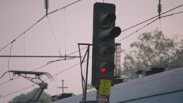 a signal changes from green to red as a train passes, mumbai, maharashtra, india. - 操車場点の映像素材/bロール