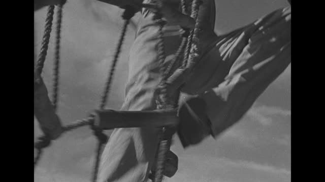 signal flags lowered aboard ship / cheerful american and british sailors lounge on deck / men climbing up and down netting on side of ship / men... - army soldier stock videos & royalty-free footage