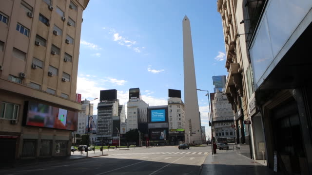 vídeos de stock e filmes b-roll de signal hanging with a message in spanish that reads 'protect your mouth with a mask' in the empty buenos aires obelisk landscape during the... - obelisk