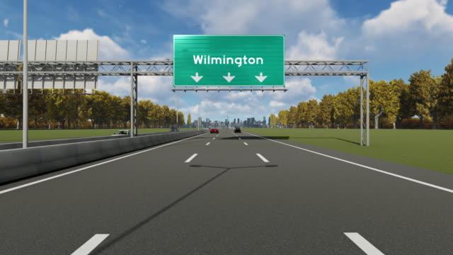 hinweis schild auf dem highway, der die einfahrt nach usa wilmington city anzeigt - wilmington north carolina stock-videos und b-roll-filmmaterial