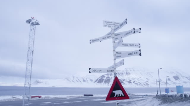 a signpost and a polar bear warning sign in longyearbyen, svalbard - polar bear stock videos & royalty-free footage