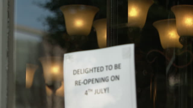 """signs about reopening and social distancing outside cafes and bars as they prepare to reopen on the 4th july after coronavirus lockdown - """"bbc news"""" stock videos & royalty-free footage"""
