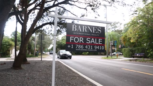Signs advertising a home for sale in Miami Florida US on Saturday November 19 2016 Shots shot of 'Barnes' realty sign near road as cars pass by pan...