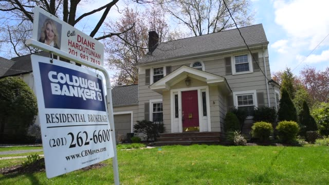 signs advertising residential real estate for sale are posted on front lawns in a suburban neighborhood in oradell, nj, u.s. on friday, may 1, 2015.... - 売り出し中点の映像素材/bロール