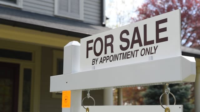 signs advertising residential real estate for sale are posted on front lawns in a suburban neighborhood in oradell, nj, u.s. on friday, may 1, 2015.... - 不動産の看板点の映像素材/bロール
