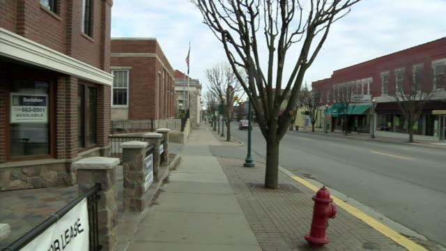 vidéos et rushes de ws pan signs advertising vacant building on main street for sale, chelsea, michigan, usa - récession