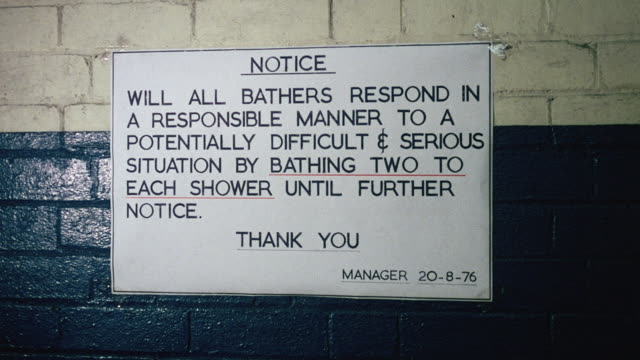 MONTAGE Signs and notices mandating water conservation for coal miners at colliery, including requiring two bathers per shower and closing one shower section / Wales, United Kingdom