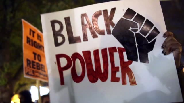 signs are seen during a rally at mt vernon square to protest against the grand jury's decision november 25 washington dc hundreds of demonstrators... - lying down stock videos & royalty-free footage