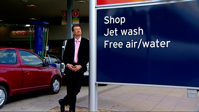 EXT Signs at Sainsbury's petrol station / reporter to camera Display of stationery on sale in supermarket with signs for '3 for 2' offer People...