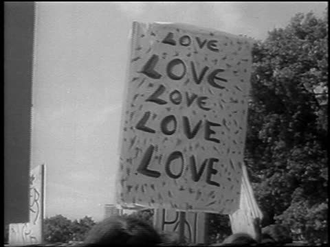 vídeos de stock e filmes b-roll de b/w 1967 signs being held at bein / hyde park london / newsreel - hippie