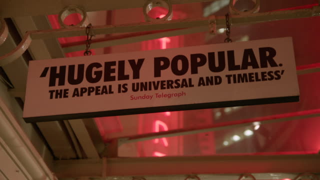 signs displaying quotes from newspaper critics reading 'hugely popular the appeal is universal and timeless' sunday telegraph and 'phenomenal a... - kritiker stock-videos und b-roll-filmmaterial