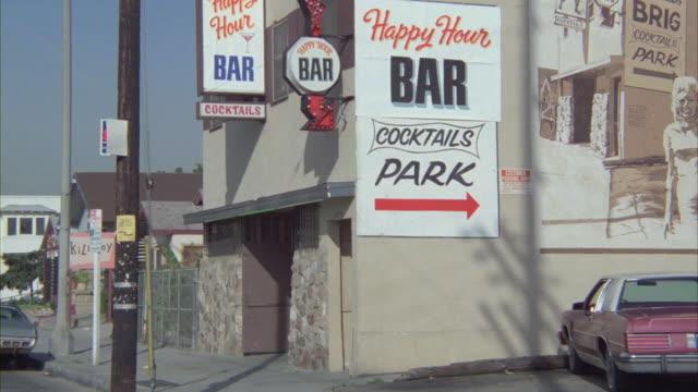 stockvideo's en b-roll-footage met signs hang on the exterior of a bar in los angeles. - bar gebouw