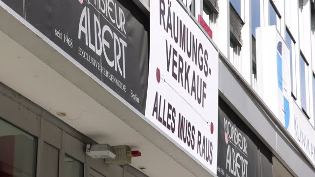 signs in the window of a clothing retailer store advertise sales and announce the general closure of the shop on kurfuerstendamm avenue during the... - sale stock-videos und b-roll-filmmaterial