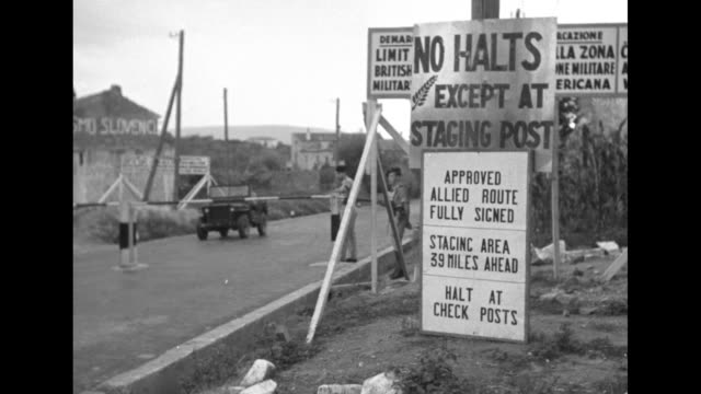 Signs next to road at checkpoint announcing Allied occupation zone / British soldier lifting guardrail as truck waits / truck drives through and...