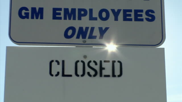PAN, ECU, Signs outside closed General Motors auto assembly plant against clear sky, Lansing, Michigan, USA