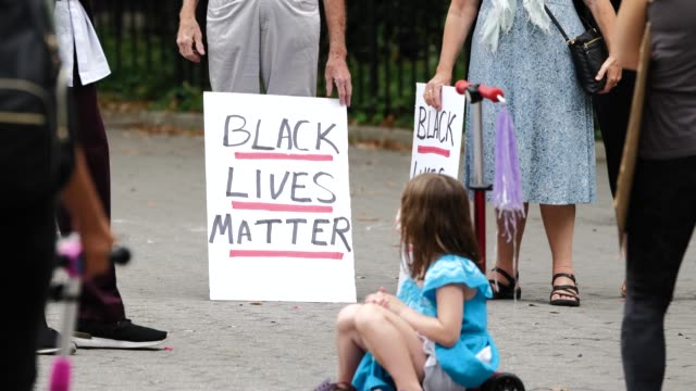 signs saying 'black lives matter' as children and their parents participate and march in solidarity with the black lives matter movement around... - generation z stock videos & royalty-free footage
