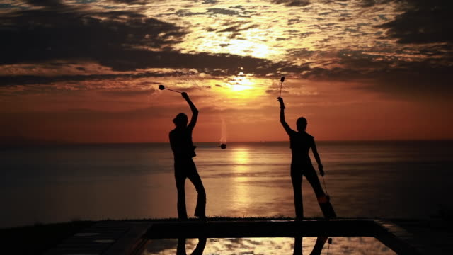 ms sihouetted couple perform poi dance together in front of fiery sunrise and ocean / montezuma, costa rica - kelly mason videos stock-videos und b-roll-filmmaterial
