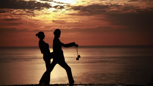 ms sihouetted couple perform poi dance together with fireballs in front of fiery sunrise and ocean / montezuma, costa rica - kelly mason videos stock videos & royalty-free footage