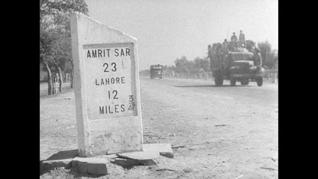 Sikh Hindu refugees walking on city street carrying belonging bundles Refugees flle area in cart caravan Trucks passing sign post Amrit Sar 23 Lahore...