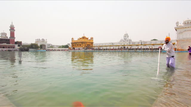 MS Sikh man cleaning pond with at Golden Temple / Amritsar, Punjab, India