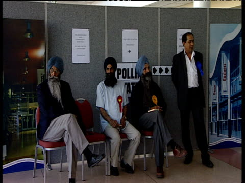 sikh men wearing different rosettes representing various political parties sit in silence on chairs in polling station for local elections slough 07... - 表す点の映像素材/bロール