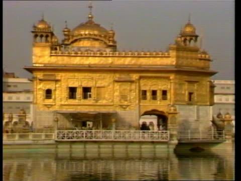vidéos et rushes de sikh temples heavily policed as they celebrate festival; india: punjab: amritsar: ext golden temple mirrored in lake tilt up temple sikh pilgrims... - fête religieuse