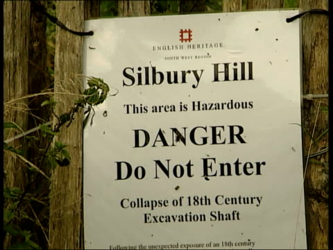 Silbury Hill prehistoric monument New research GV Mound FADE MS 'Footpath closed' sign on fence around Silbury Hill CMS Hazard warning sign on fence...