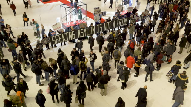 """a silent antitrump protest activist from rise and resist rally at the oculus westfield world trade center holding a giant banner that reads """"seeking... - other stock videos and b-roll footage"""