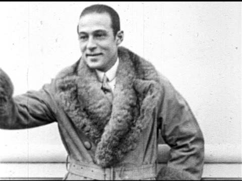 silent film star rudolph valentino standing on deck of ocean lines dressed in fur trimmed coat, valentino talking . - 1925 stock videos & royalty-free footage