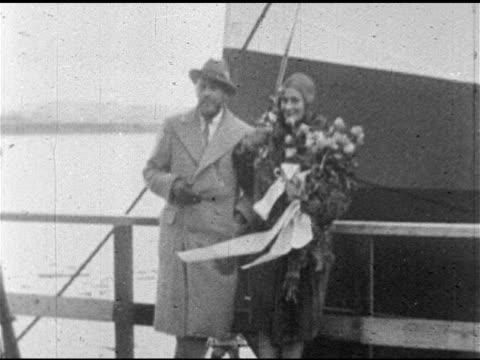 vídeos y material grabado en eventos de stock de silent film stars actor john barrymore & actress dolores costello dressed in coats standing on deck of ocean liner, dolores holding bouquet of roses.... - 1928