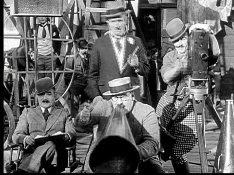 vídeos de stock e filmes b-roll de 1924 b/w ms silent movie director (vernon dent) shouting into megaphone, while cameraman (andy clyde) films action and another man (charles murray) watches / usa - sala de imprensa