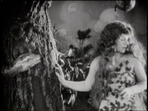 a silent movie reenacts adam and eve in the garden of eden and the serpent's attempt to tempt eve - biblical event stock videos & royalty-free footage