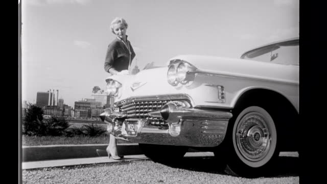 / Silent news film showing a pretty blonde driving a 1958 Series 62 Cadillac convertible / WS Cadillac driving toward camera on a suburban boulevard...