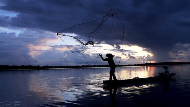 hd: silhouette asian fisherman on wooden boat casting a net for catching freshwater fish in nature river in the early morning before sunrise - netting stock videos and b-roll footage