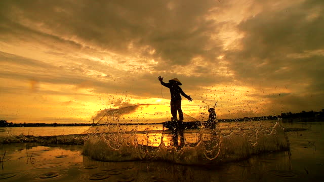 HD: Silhouette Asian fisherman on wooden boat casting a net for catching freshwater fish in nature river in the early morning before sunrise