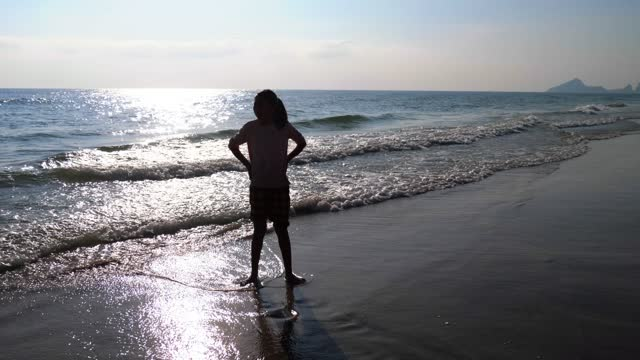 silhouette asian girl enjoying on the beach in the morning, lifestyle concept. - back lit stock videos & royalty-free footage