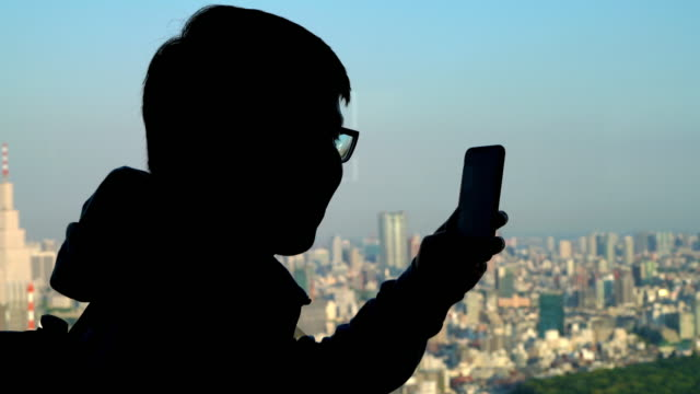 silhouette asian man take a photo of tokyo cityscape view via smartphone - mack2happy stock videos and b-roll footage