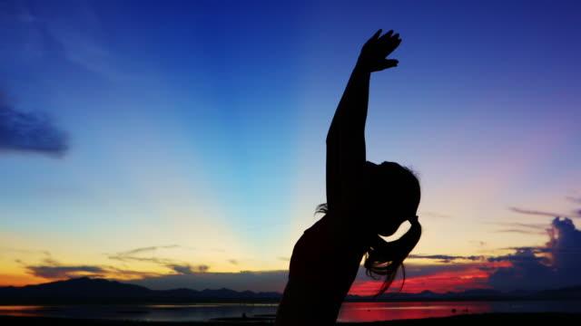 vídeos de stock, filmes e b-roll de silhueta mulheres asiáticas estão se exercitando com yoga fora perto do rio à noite. - equilíbrio