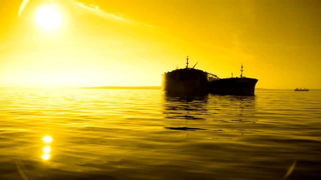 vídeos de stock e filmes b-roll de silhueta ao pôr do sol-tanque com âncora no mar - ancorado