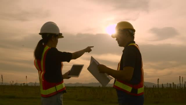 silhouette in der dämmerung architekten und ingenieure untersuchen die weitläufigen außenraum-baupläne vor ort, diskutieren sie die arbeit auf der baustelle the professional engineer checking work. - bauarbeiterhelm stock-videos und b-roll-filmmaterial