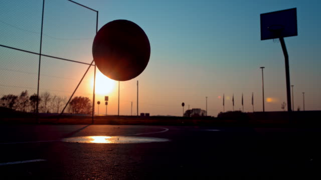ms super slow motion silhouette basketball bouncing on outdoor basketball court at sunset - bouncing stock videos & royalty-free footage