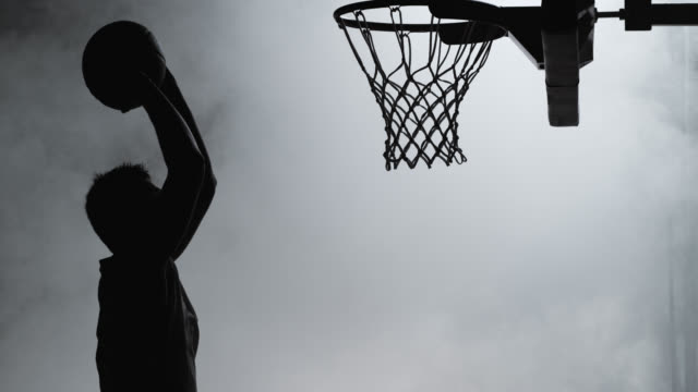 stockvideo's en b-roll-footage met slo mo of silhouette basketball player dunking the ball - studio shot