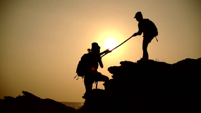 silhouette  between two teen asian female climbers with a rope helping climbers on the top of the mountain. - trust stock videos & royalty-free footage