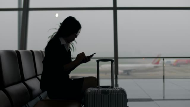 silhouette business woman at departure area - examining stock videos and b-roll footage